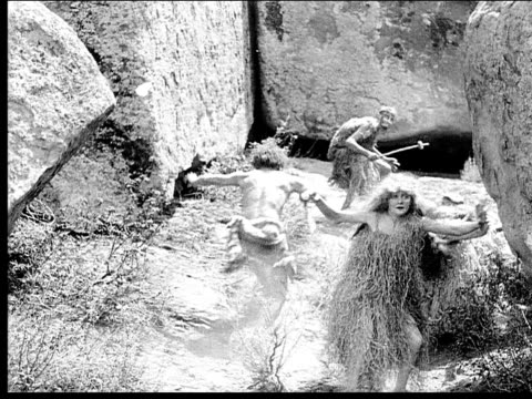 1914 b/w wide shot cavemen running past boulders through passageway and grabbing cavewoman - forearm stock videos and b-roll footage
