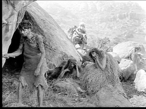 1914 B/W Wide shot Cavemen standing outside cave