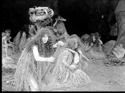 1914 B/W Wide shot Cavewoman brandishing weapon and running around cave