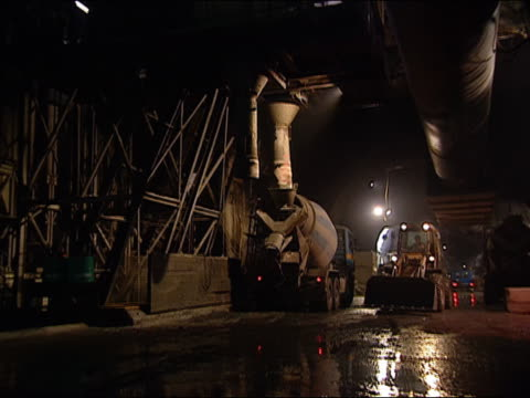 2002 wide shot cement mixer spinning and bulldozer moving toward camera during construction in lotschberg tunnel/ zoom in medium shot spinning cement mixer/ mitholtz, switzerland - cement mixer stock videos & royalty-free footage
