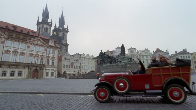 wide shot chauffeur driving couple in vintage convertible car in tour of old town square / prague - prague old town square stock videos & royalty-free footage