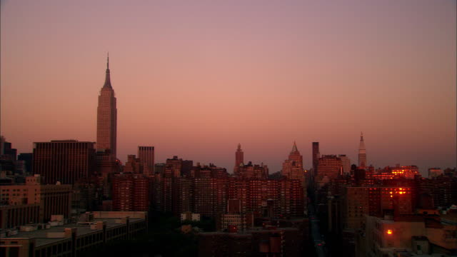 wide shot chelsea skyline with empire state building at dusk / nyc - chelsea new york stock videos & royalty-free footage