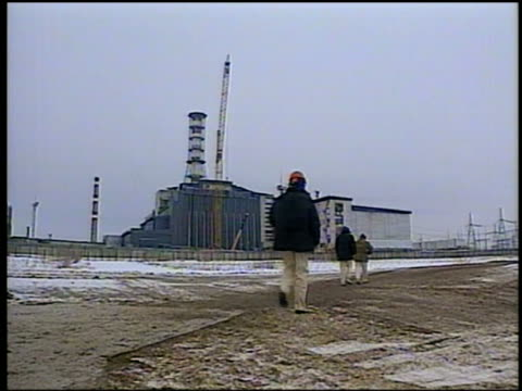 1996 wide shot chernobyl nuclear plant / men walking past in foreground / 10 year anniversary of disaster - 身体保護用品点の映像素材/bロール