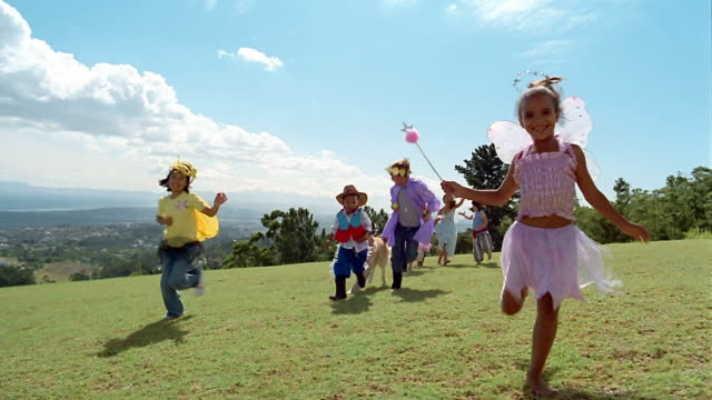 vidéos et rushes de wide shot children in costumes and dog running across field toward cam / somerset west, south africa - costume