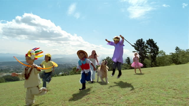 vídeos y material grabado en eventos de stock de wide shot children in costumes running across field/ low angle children and dog leaping/ somerset west, south africa - jugar