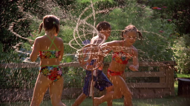 wide shot children in swimsuits running around revolving sprinkler / girl hopping toward cam / new york - sprinkler stock videos & royalty-free footage
