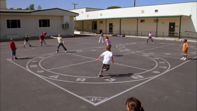 wide shot children playing game of kickball on playground court - school yard stock videos and b-roll footage
