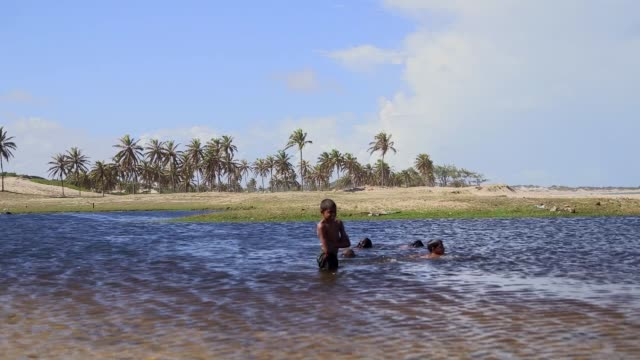 Wide Shot children playing in water at the beach General views from a beach in Natal Brazil shot on December 8th 2014 Natal is located on the...