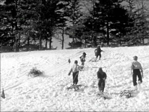 1945 wide shot children pulling sleds up snowy hill and riding down/ audio - sledge stock videos & royalty-free footage