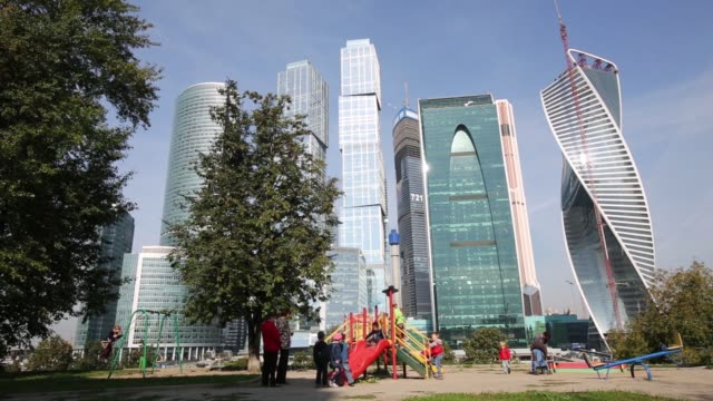 vídeos de stock, filmes e b-roll de wide shot children run through a park as buildings in the moscow international business center also known as moscow city stand on the skyline in the... - produto interno bruto