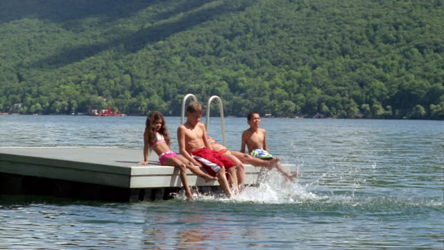 Wide shot children sitting on edge of raft kicking water / Canandaigua Lake, New York