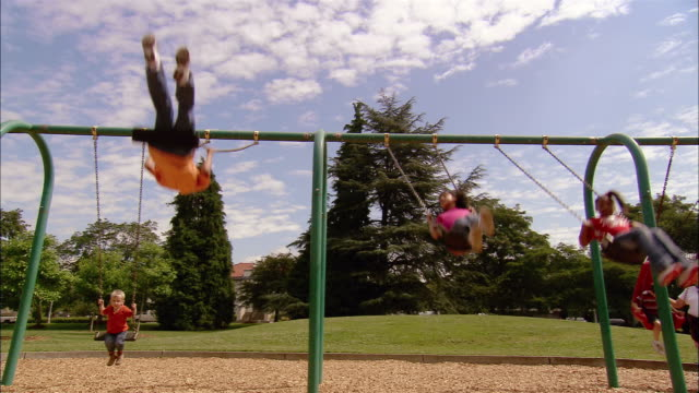 vídeos y material grabado en eventos de stock de wide shot children swinging on swing set in park / mother pushing young boy - columpiarse