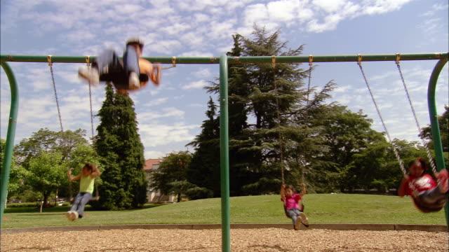 vídeos de stock e filmes b-roll de wide shot children swinging on swing set in park - baloiço