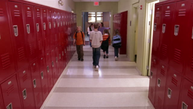 Wide shot children walking in primary school corridor/ girl putting backpack in locker and walking away/ Goram, Maine