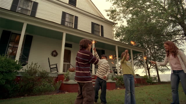 wide shot children waving sparklers in front yard of house - fourth of july stock videos & royalty-free footage