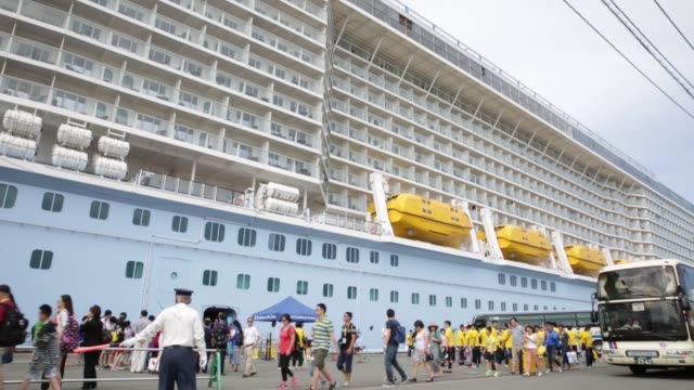 Wide shot Chinese tourists walk past the Quantum of the Seas Cruise ship operated by Royal Caribbean Cruises Ltd's cruise line brand Royal Caribbean...