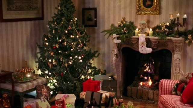 wide shot christmas tree and presents in living room with fire in fireplace - living room stock videos & royalty-free footage