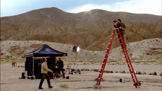 Wide shot cinematographer standing on tall ladder setting up shot / director walking up to him and giving instruction / Red Rock Canyon State Park, California