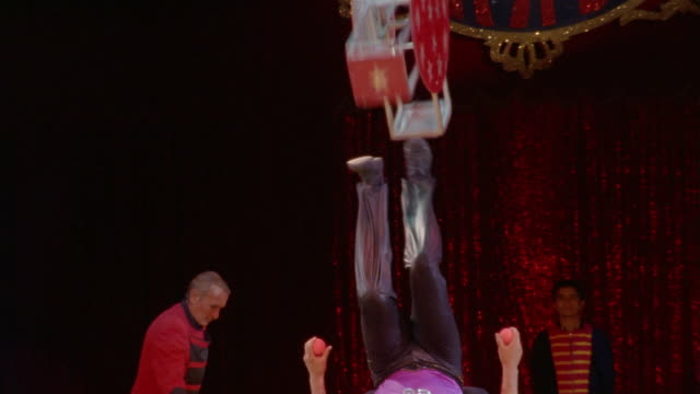 wide shot circus perfomer lying on back, spinning apparatus on feet and juggling balls simultaneously/ mexico - juggling stock videos & royalty-free footage