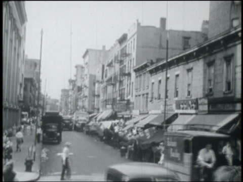 B/W 1949 wide shot city street with awnings on storefronts / NYC