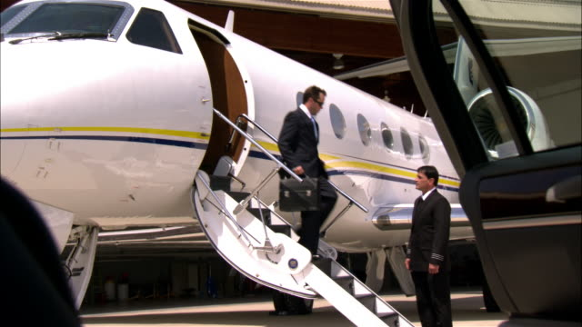 Wide shot - close-up Businessman exiting private airplane near pilot, and walking toward limousine / Long Beach, California, USA