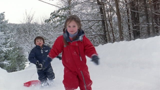 wide shot - close-up girl and boy pulling sled and running in snow / franconia, grafton county, new hampshire, usa - スキーウェア点の映像素材/bロール
