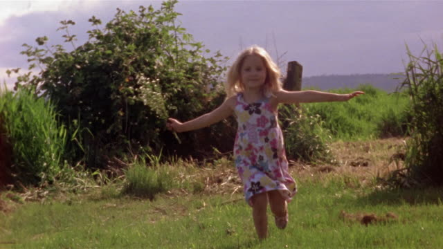wide shot - close-up girl runing in field and holding bunch of flowers / des moines, king county, washington, usa - 小学校低学年点の映像素材/bロール