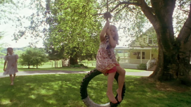 wide shot - close-up one girl pushing another on tire swing near house / des moines, king county, washington, usa - tyre swing stock videos & royalty-free footage