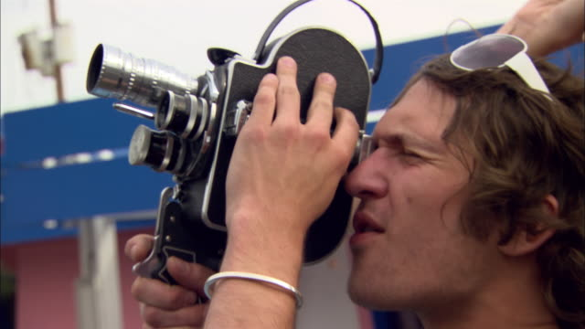 wide shot - close-up pan young man with movie camera filming young woman in diamond inn motel parking lot/ las vegas, nevada, usa - スウィッシュパン点の映像素材/bロール