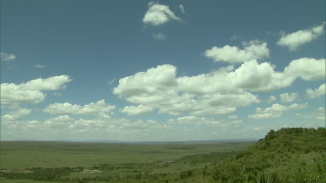 wide shot - clouds drifts above an african savanna / kenya - horizont stock-videos und b-roll-filmmaterial
