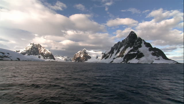 wide shot clouds floating above snowcapped glaciers along coast of antarctic sea/ antarctica - boat point of view stock videos & royalty-free footage
