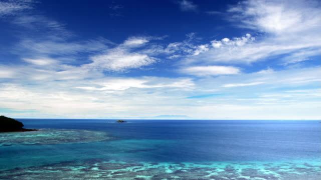 wide shot clouds moving across sky over a coral reef in pacific ocean / fiji - horizont stock-videos und b-roll-filmmaterial