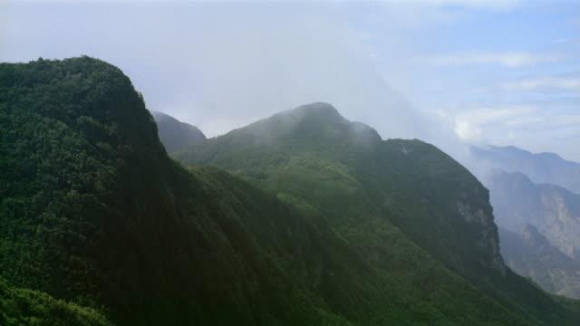 Wide shot clouds passing over green mountainside / Venezuela