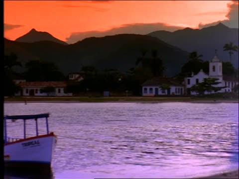 vídeos de stock e filmes b-roll de wide shot pan of coastal village with mountains in background / brazil - cinematografia