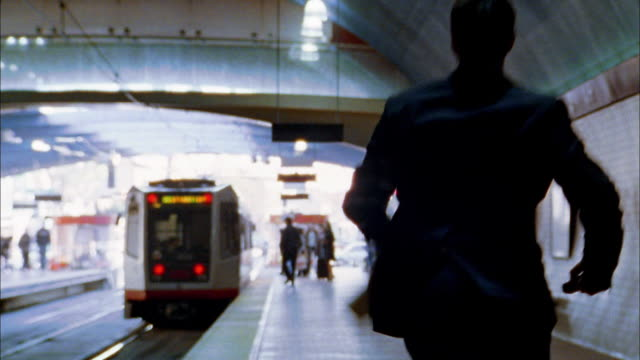 wide shot commuter running to catch train - stazione della metropolitana video stock e b–roll