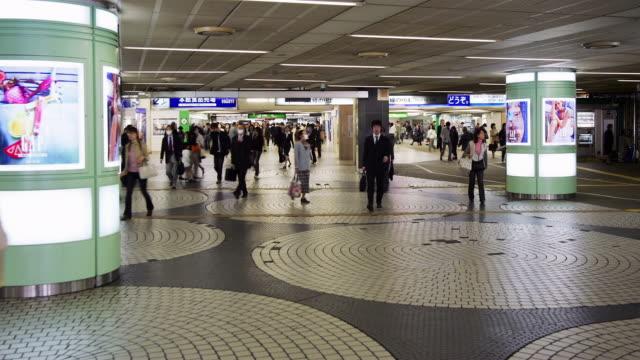 vídeos de stock, filmes e b-roll de wide shot commuters passing through busy shinjuku metro station / tokyo, japan - excesso de trabalho