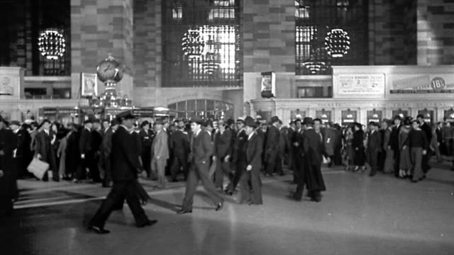 b/w wide shot commuters walking in grand central station with clock / new york city - grand central station manhattan stock videos & royalty-free footage