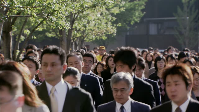 Wide shot commuters walking outside Tokyo Station on way to work in morning / Tokyo