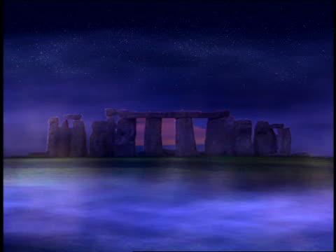 vídeos de stock, filmes e b-roll de wide shot composite sunrise behind stonehenge surrounded by mist / england - céu romântico