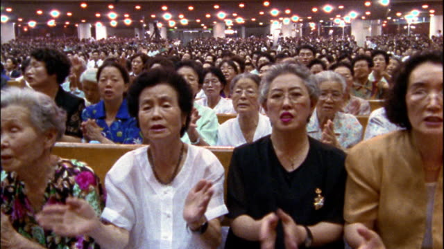 wide shot congregation church singing and clapping hands / south korea - in den fünfzigern stock-videos und b-roll-filmmaterial