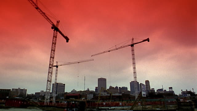 wide shot construction site / time lapse cranes turning and workers moving / memphis - desaturated stock videos & royalty-free footage