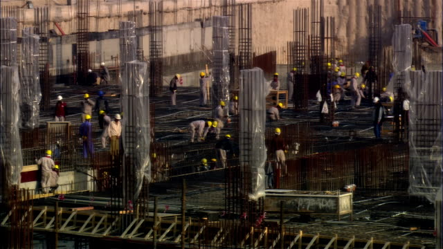 wide shot construction workers/ dubai - building activity stock videos & royalty-free footage
