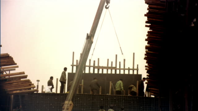 Wide shot construction workers guiding wooden frame into place as crane lowers it/ Beijing, China
