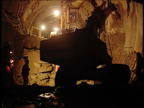 2002 wide shot construction workers standing around as construction vehicle scrapes at wall of gotthard tunnel before backing up toward camera/ elevated backhoe in background picking up dirt/ bodio, switzerland - digging点の映像素材/bロール