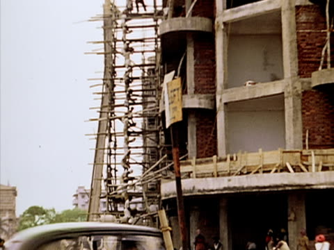 1939 wide shot constructions workers passing materials up scaffolding/ bombay, india  - wide stock videos and b-roll footage