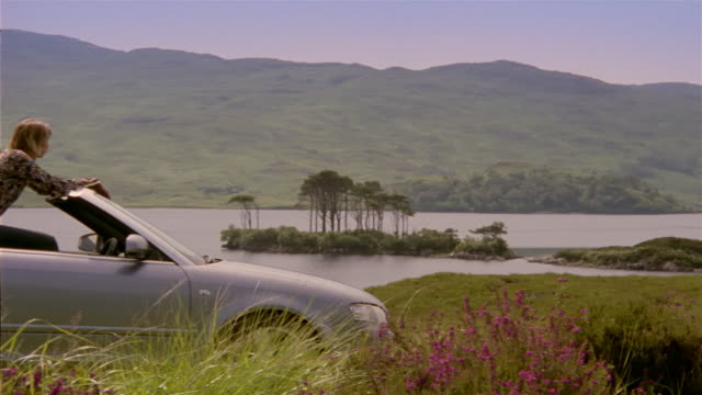 wide shot countryside with hills and lake / panning to woman hopping out of convertible and hugging man / looking at view and dragging him off / scotland - 年の差カップル点の映像素材/bロール