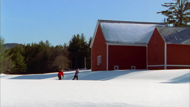 wide shot couple cross country skiing past red barn - skijacke stock-videos und b-roll-filmmaterial