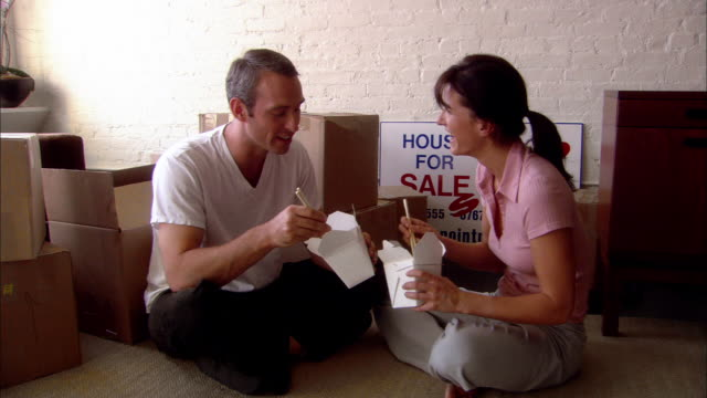 wide shot couple eating chinese food from takeout containers while sitting among moving boxes - take away food stock videos and b-roll footage