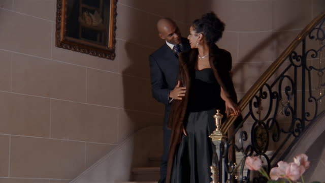 Wide shot couple in evening wear descending marble staircase
