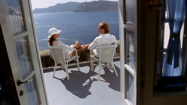 wide shot couple lounging on balcony and looking at aegean sea / toasting / kissing / santorini, greece - paar mittleren alters stock-videos und b-roll-filmmaterial